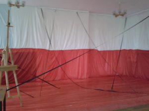 Szkolna aula przygotowana na uroczysty apel z okazji Dnia Niepodległości.